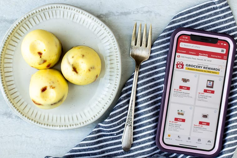 Egg bites on a white plate next to a phone with the Safeway app on it and a striped napkin and fork over a white backdrop