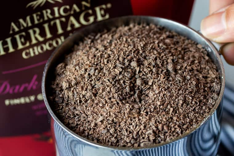 A silver measuring cup full of grated chocolate with the AMERICAN HERITAGE Chocolate package in the background