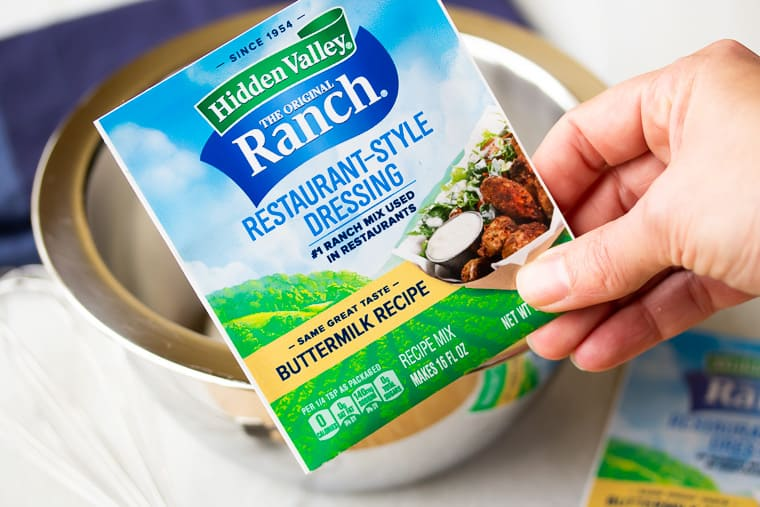 A hand holding up a packet of Ranch Dressing Mix with a silver bowl, blue napkin, and second packet in the background