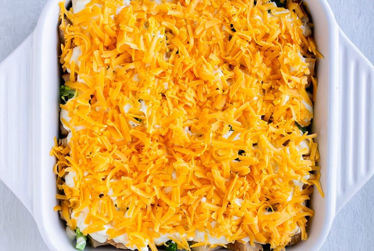 Shredded cheese on top of a cheese sauce, broccoli and chicken in a white casserole dish