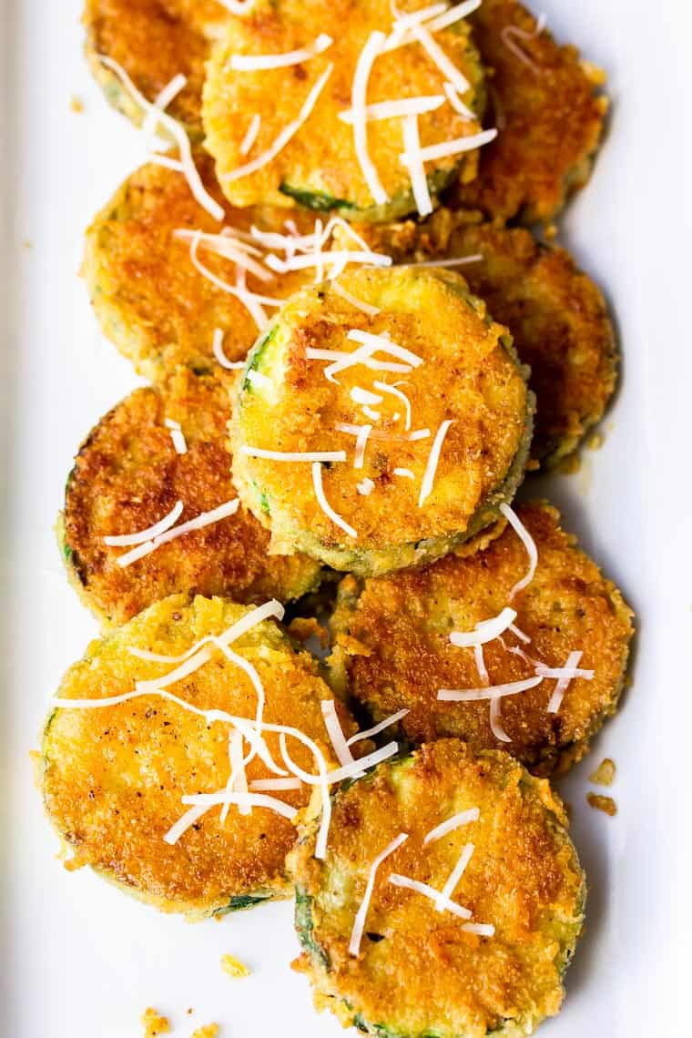 CLose up of fried zucchini topped with extra Parmesan cheese