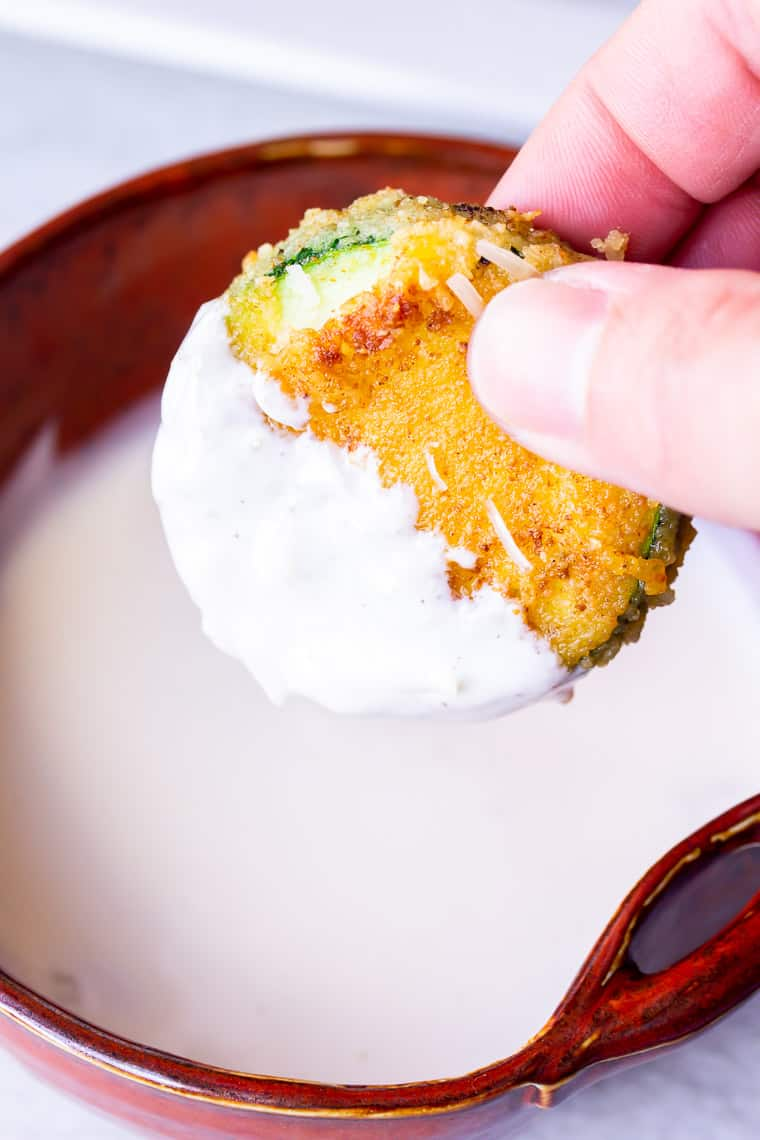 Close up of a fried zucchini round being dipped in roasted garlic aioli