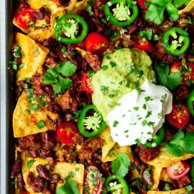 Close up of sheet pan restaurant style nachos with a dollop of sour cream and a dollop of guacamole in the middle