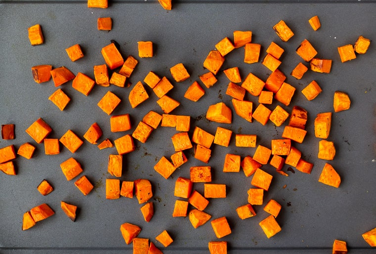 Roasted diced sweet potatoes on a gray sheet pan