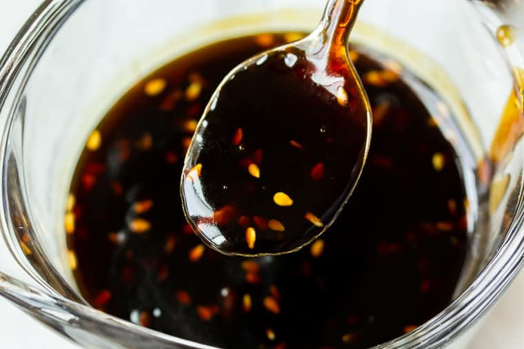 Close up of teriyaki sauce on a spoon over a glass jar filled with more sauce
