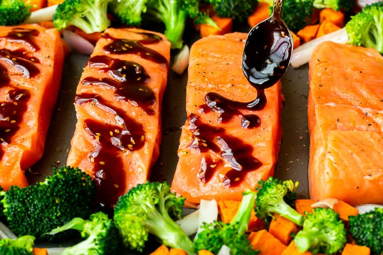 Teriyaki sauce being drizzled over salmon fillets on a gray sheet pan with broccoli around it