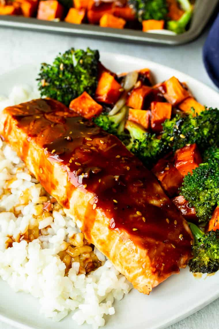 A teriyaki salmon fillet over white rice with broccoli and sweet potatoes with a baking tray in the background