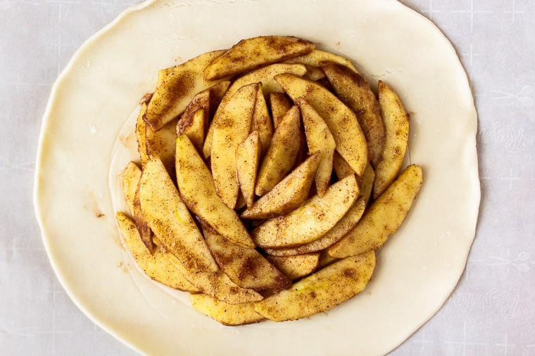 Apple slices layered onto the center of a pie crust on parchment paper