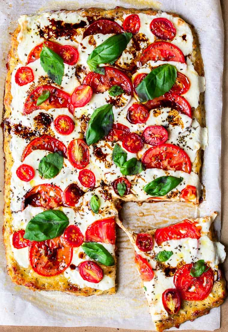 A Caprese Pizza with a slice being pulled away
