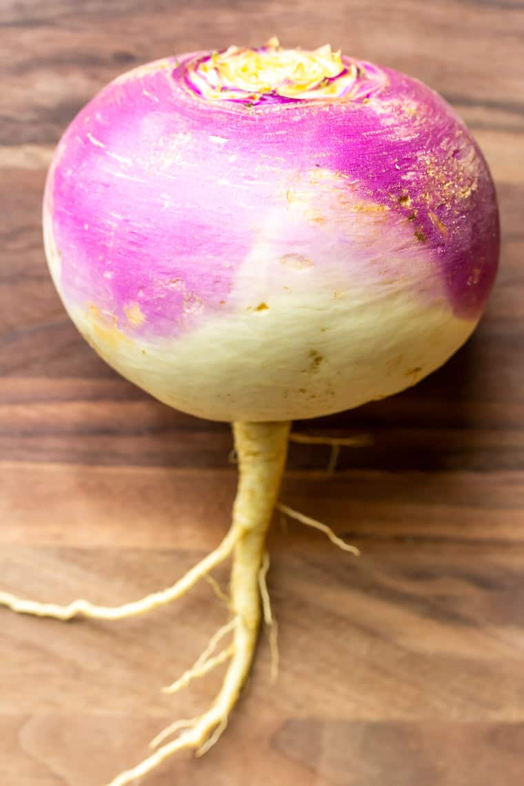 A single whole turnip on a wood cutting board
