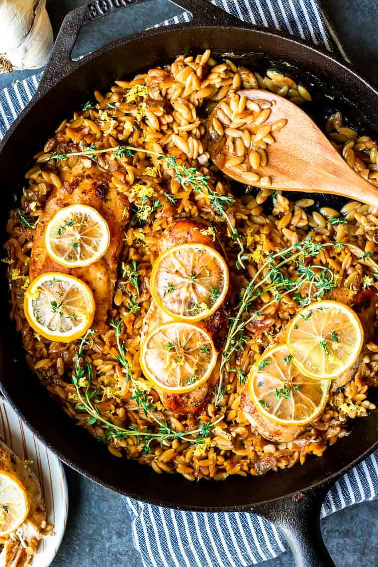 Chicken breasts with lemon slices in a skillet full of orzo with a wood spoon in it. There is a blue an white striped towel under the cast iron pan and part of a bulb of garlic and plate of chicken in the background all over a blue gay background