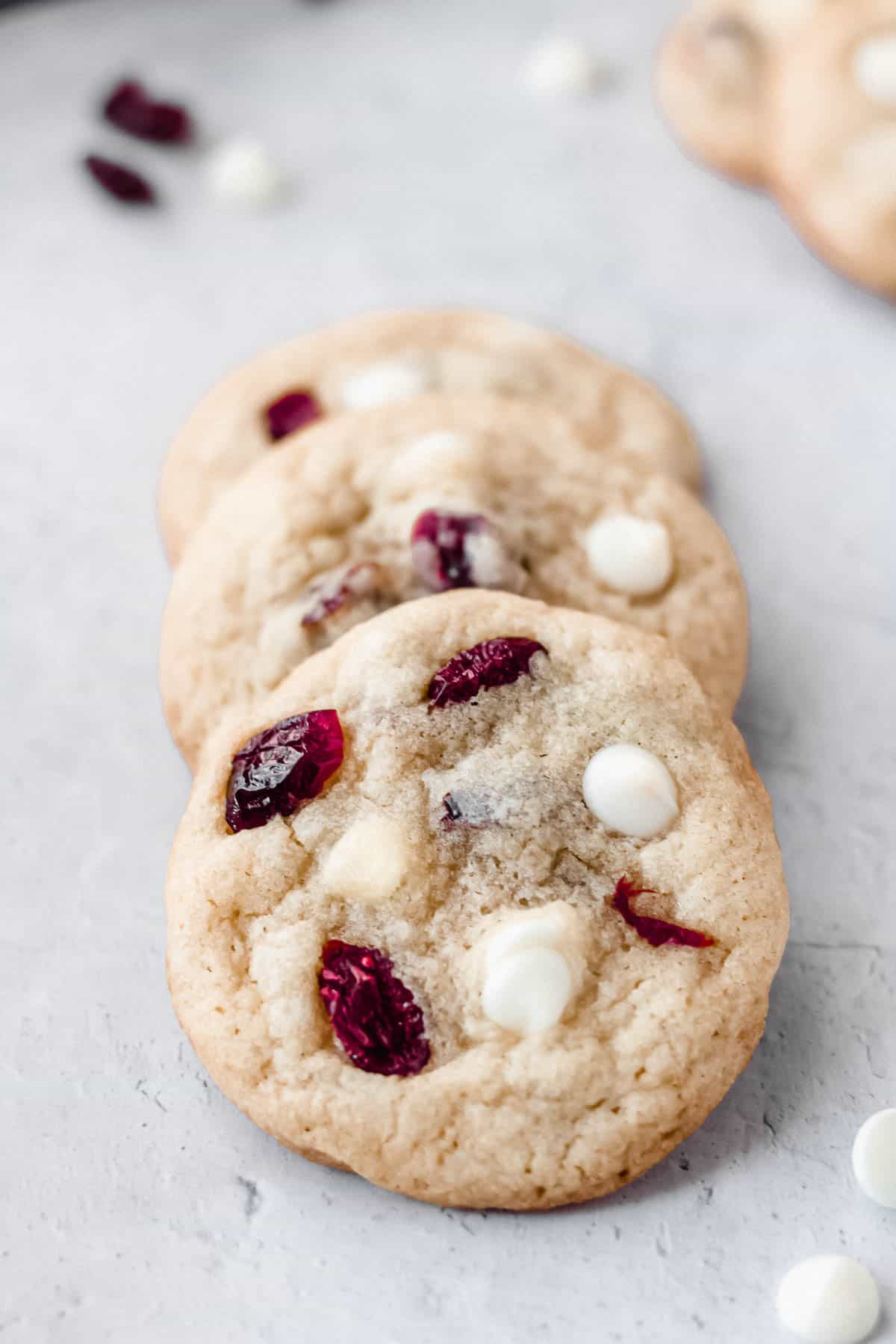 3 white chocolate chip cranberry cookies layered over each other on a white background with extra chips and cranberries around them