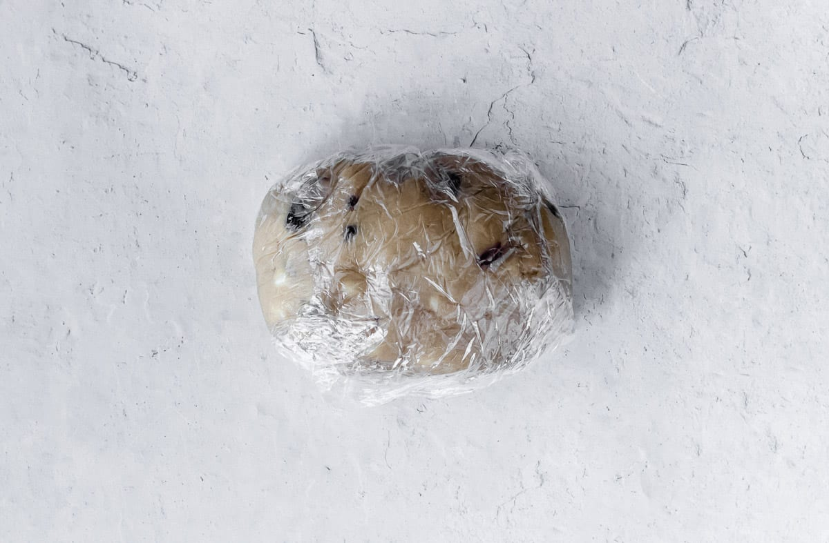 Cookie dough wrapped in plastic on a white background