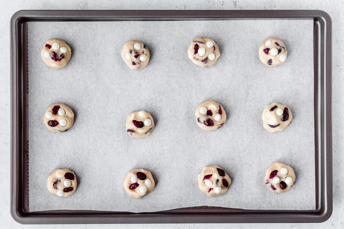 White chocolate chip cranberry cookie dough balls on a parchment paper lined baking sheet