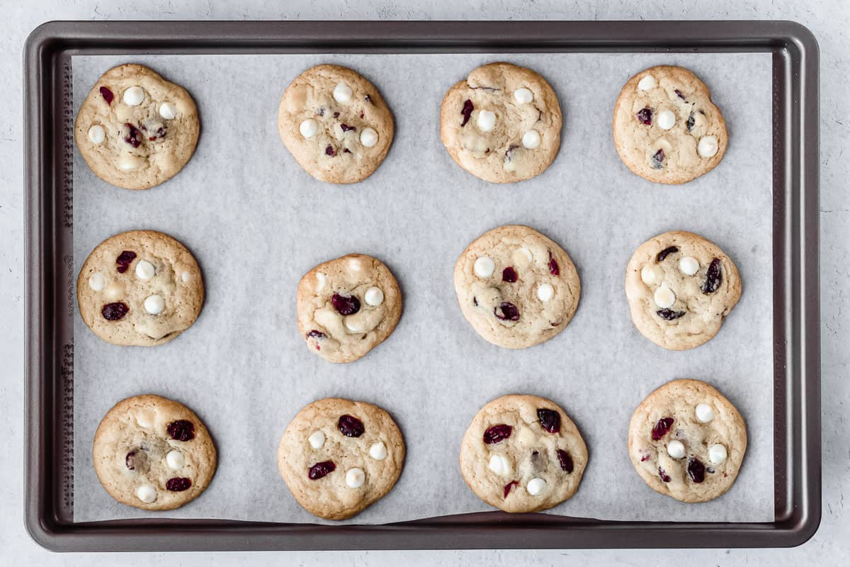 Baked white chocolate chip cranberry cookies on a parchment paper lined baking sheet