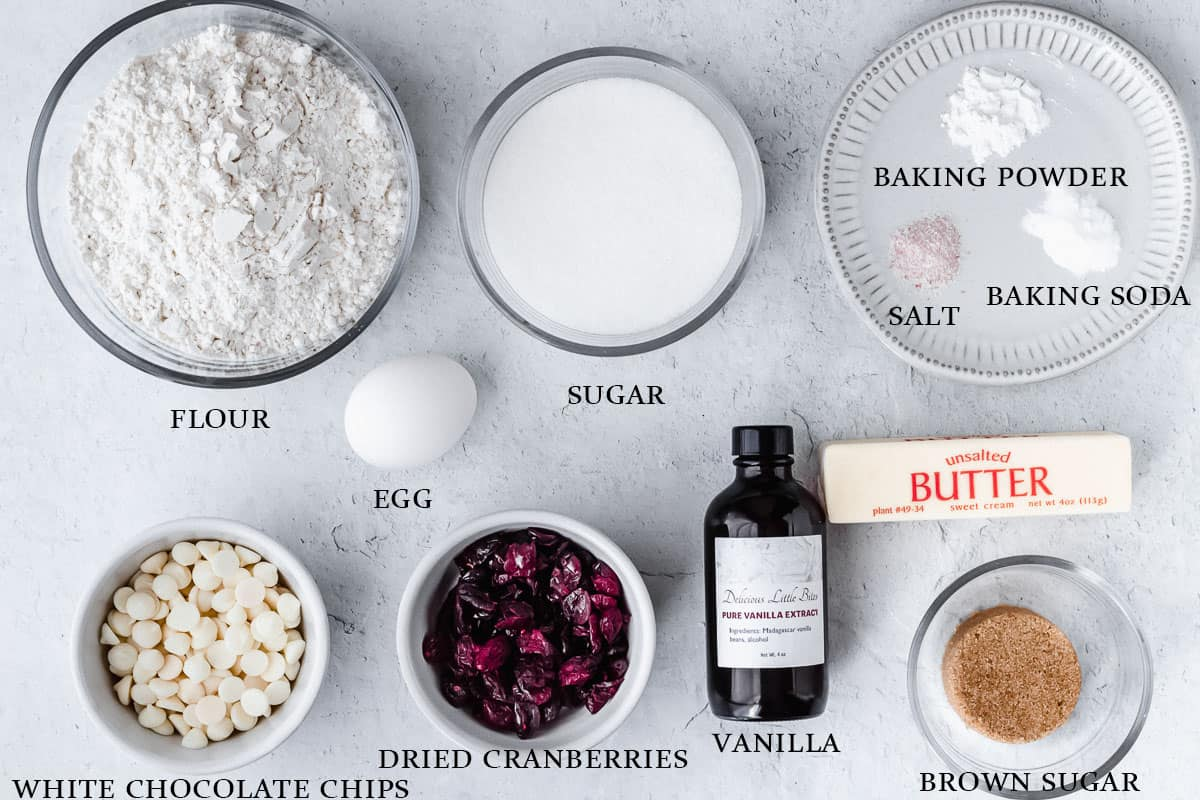 Ingredients for white chocolate chip cranberry cookies on a white background with labels