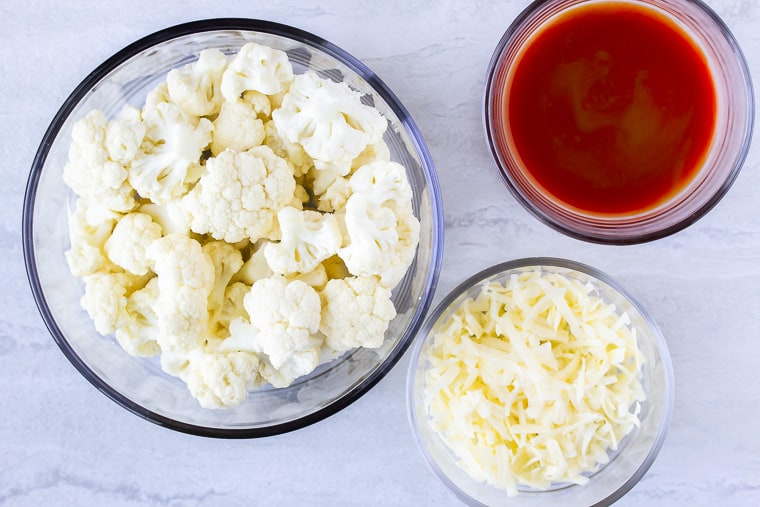 cauliflower, cheese, and buffalo sauce in glass bowls over a white background