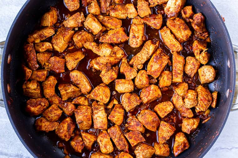 Chicken and Enchilada seasonings cooking in a black skillet over a white background