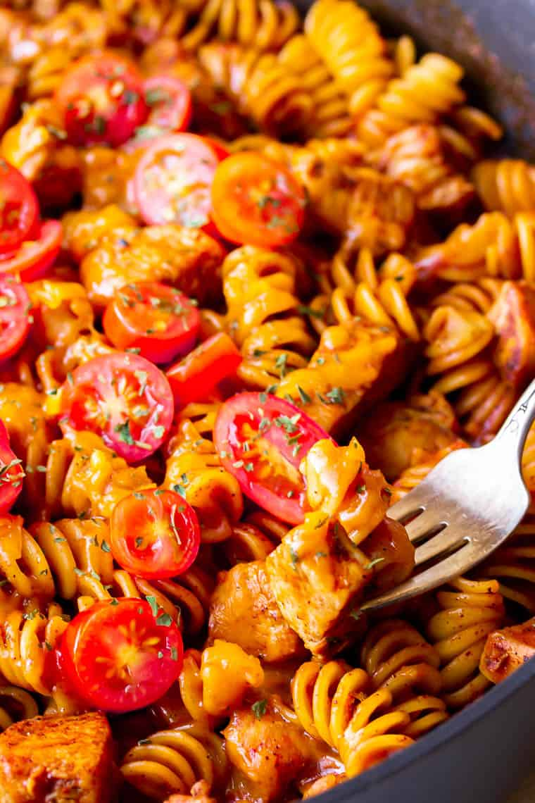 Close up of a bite of Cheesy Chicken Enchilada Pasta being taken out of a pan