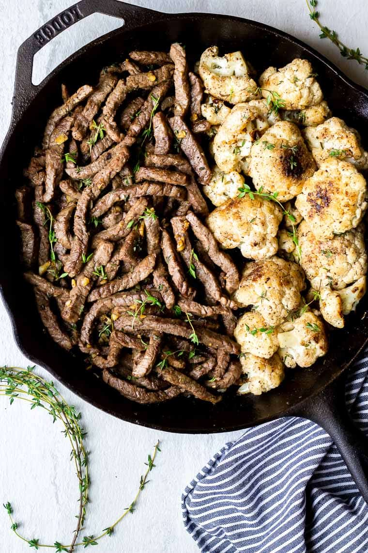 A cast iron skillet with garlic butter steak bites on one side and cauliflower florets on the other with a blue and white striped napkin and fresh thyme sprigs all around over a white background