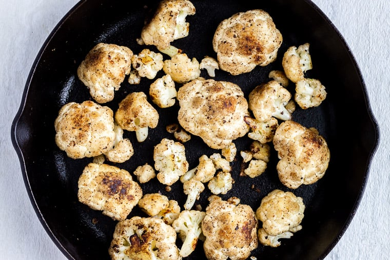 Browned cauliflower florets in a cast iron skillet over a white background