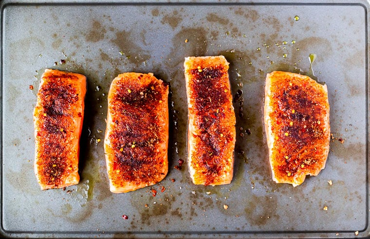 4 pieces of salmon with seasoning on them on a baking sheet
