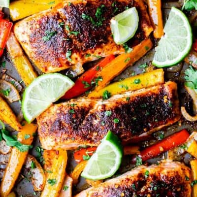 Overhead of sheet pan salmon fajitas with peppers and onion on a baking sheet with limes and cilantro