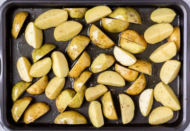 Raw potato wedges on a baking sheet