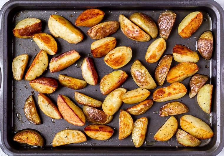 Roasted potato wedges on a baking sheet