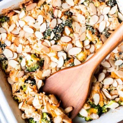 Overhead of broccoli chicken bake in a square, white casserole dish with a wood turner lifting up a scoop over a wood background with a blue and white striped towel