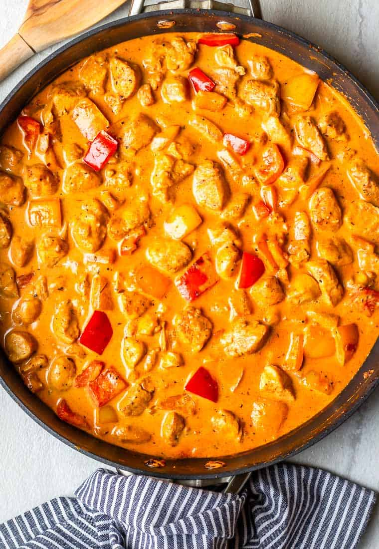 Creamy Cajun Chicken and peppers in a skillet over a white background with a blue and white towel and wood spoon around it