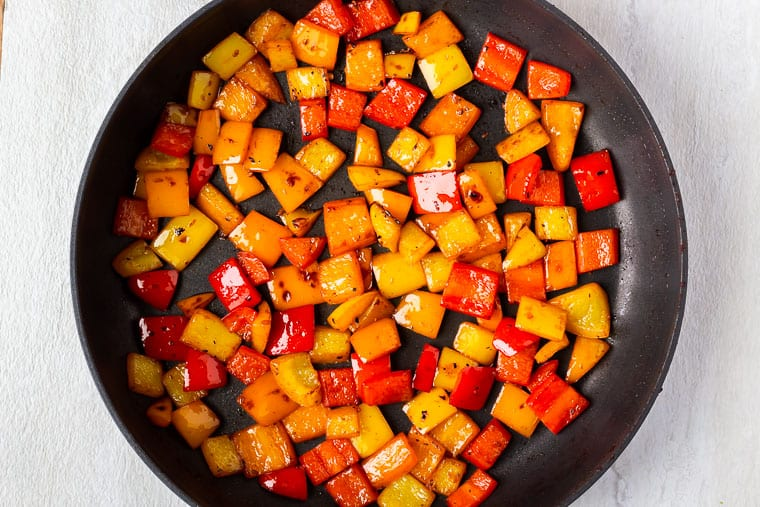 Orange, yellow and red bell peppers chunks cooking in a large black skillet over a white background
