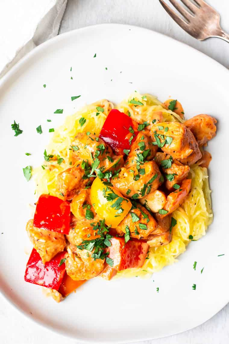 Overhead view of A white plate of Keto Creamy Cajun Chicken and peppers over a white background with a white napkin and fork