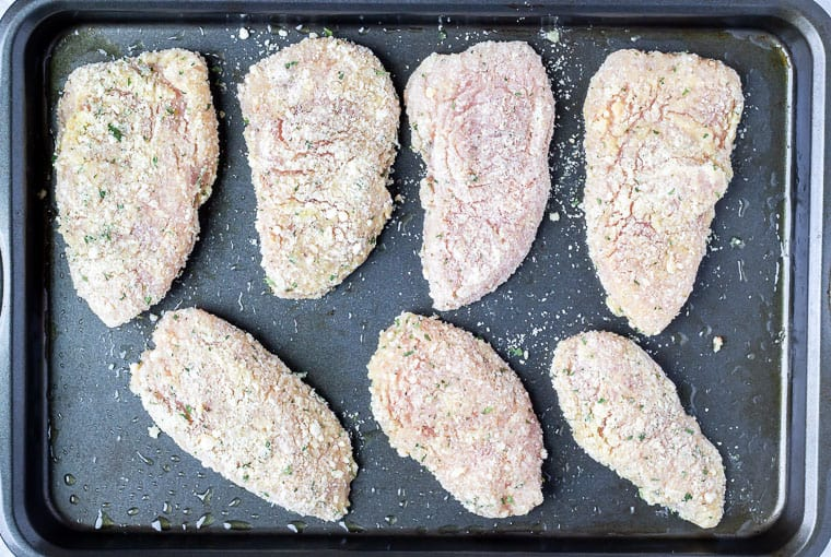 Prepared turkey cutlets on a baking sheet before baking.