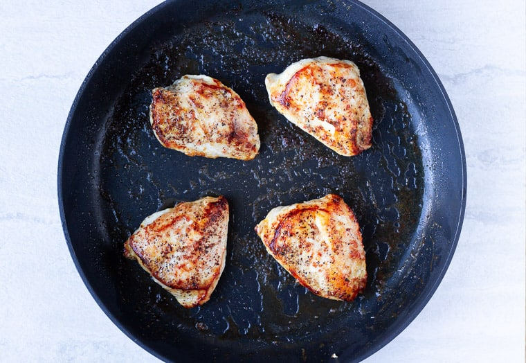 4 seared chicken breasts in a black skillet over a white background