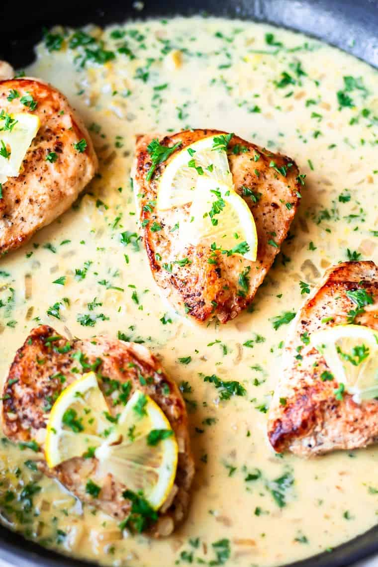 Close up of 4 Lemon Garlic Chicken breasts in a skillet with lemon garlic sauce