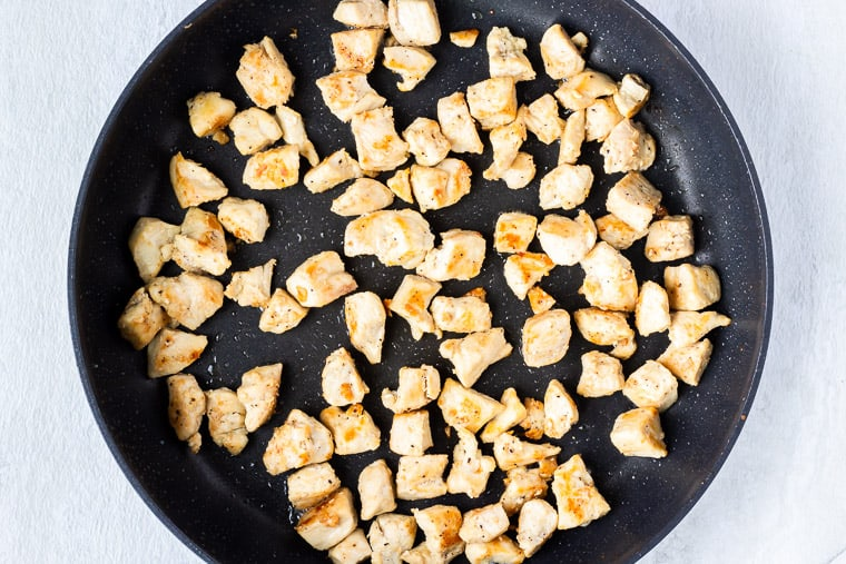 Cooked cubes of chicken in a large skillet over a white background