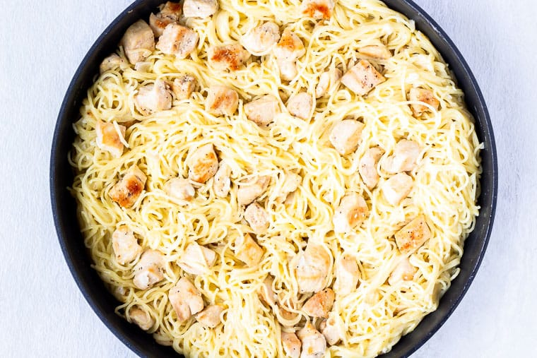Angel hair pasta and cubed chicken in a large skillet over a white background