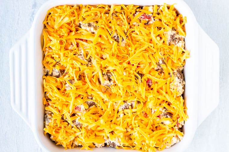 Sausage mixture in a square, white casserole dish topped with shredded cheddar cheese over a white background
