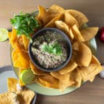 White Nectarine Salsa in a gray bowl surrounded by tortillas chops on a wood table