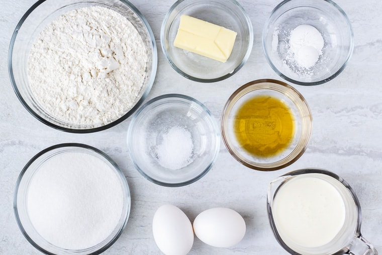Ingredients needed to make mini vanilla cupcakes in glass bowls on a white background