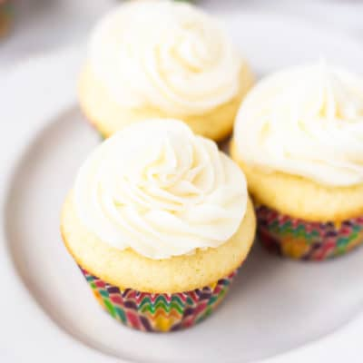 3 mini vanilla cupcakes on a small white plate with 3 more blurred in the background on a white backdrop