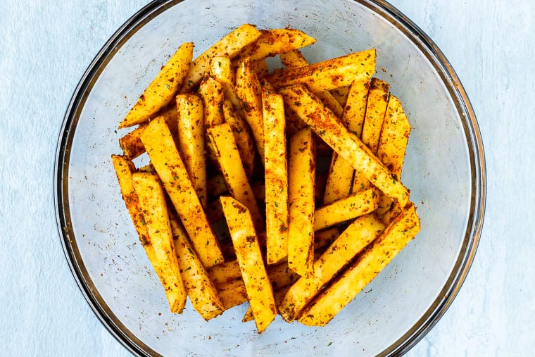 raw rutabaga fries tossed in olive oil and seasonings in a glass bowl over a white background