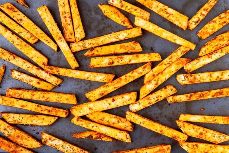 Raw rutabaga fries on a baking sheet