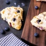 A white Chocolate Chip Blueberry Scone on a gray background with a blue and white striped towel, a small blue bowl of vanilla glaze, loose blueberries, and a wood board with 2 scones and blueberries on it all around