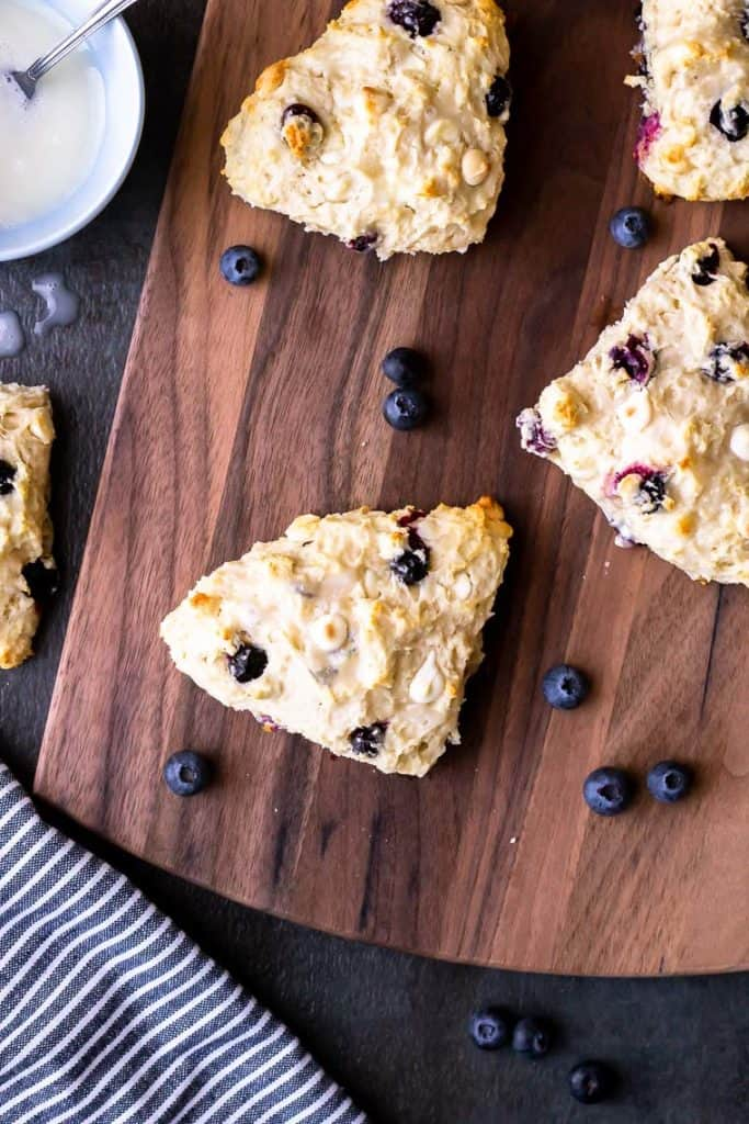 4 White Chocolate Chip Blueberry Scones on a wood board over a gray background with a small blue bowl of vanilla glaze, another scone, loose blueberries, and a blue and white striped towel around it