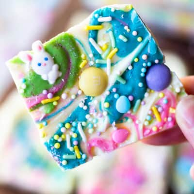holding up a piece of white chocolate easter bark