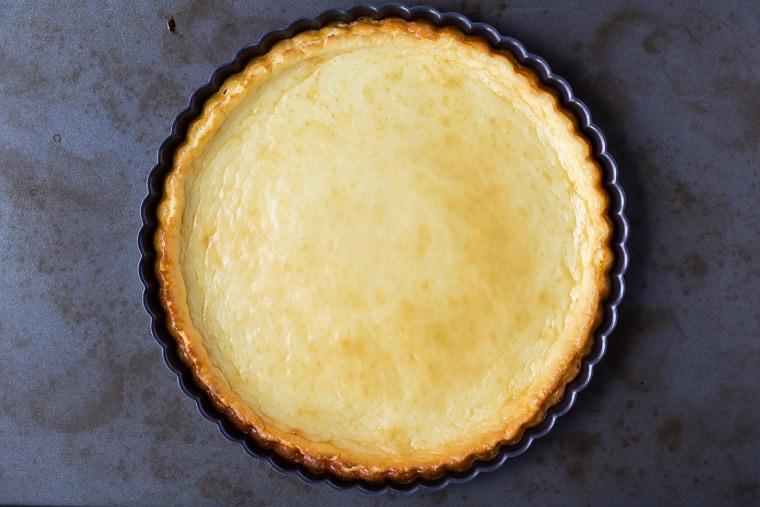 Baked Crustless cheesecake in a tart pan over a baking sheet