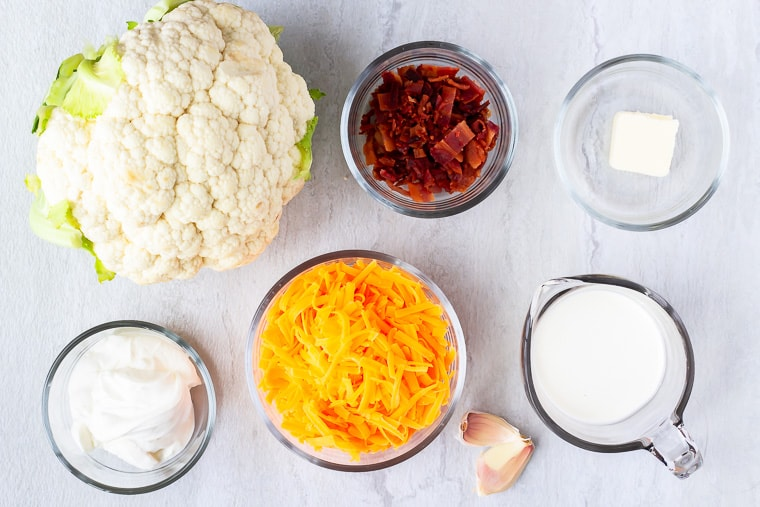 Ingredients needed to make loaded mashed cauliflower in glass bowls over a white background