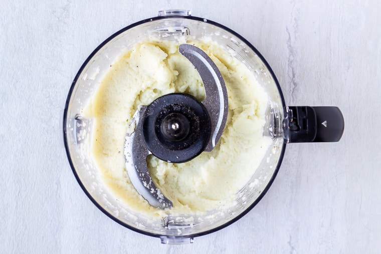 Pureed cauliflower in a food processor with a blade over a white background